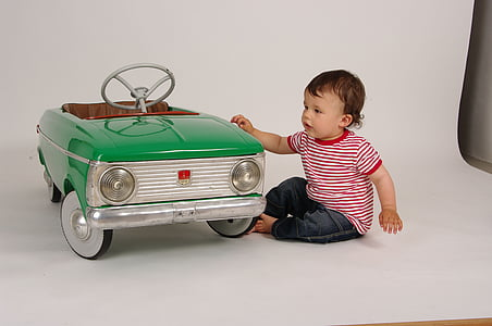 toddler with red and white striped shirt next to teal ride-on vehicle