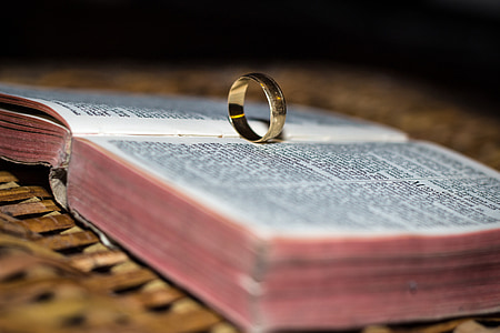 gold-colored ring on opened Bible selective focus photo