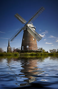 brown windmill beside the body of water