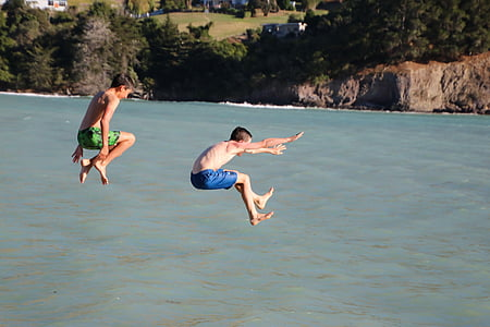 two boys jumping on body of water