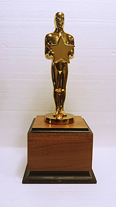 man holding star gold trophy on brown wooden base