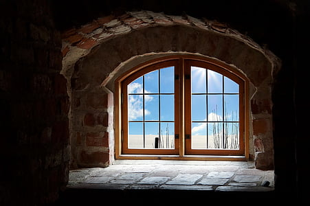 brown wooden window on bricked house