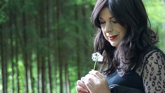 woman holding white petaled flower during daytime