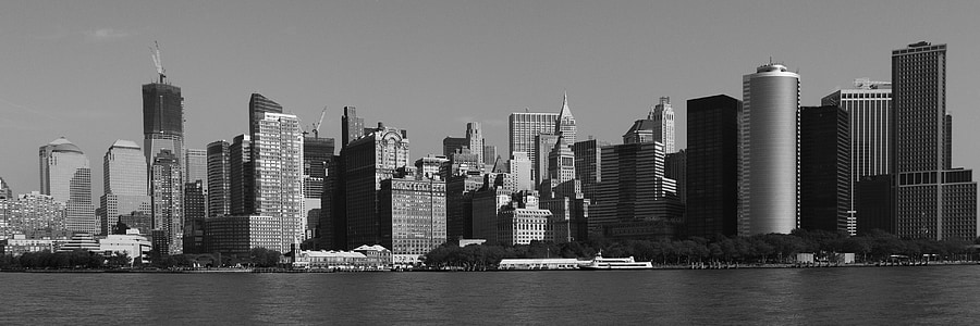 grayscale photo of cityscape by water