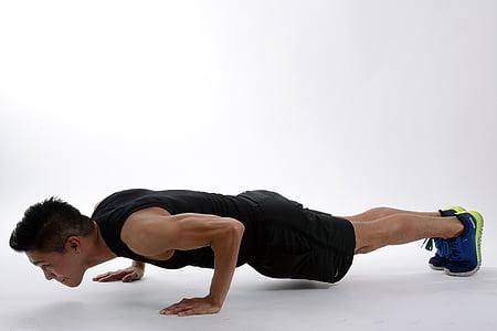 man wearing black sleeveless shirt doing push ups