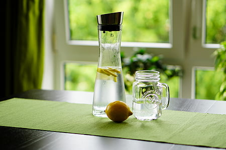 shallow focus photography of sliced lemon in glass bottle with water