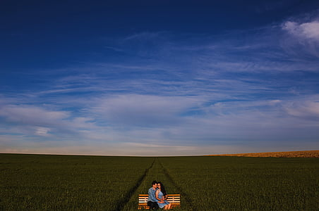 man and woman sitting on bench overlooking green field during daytime