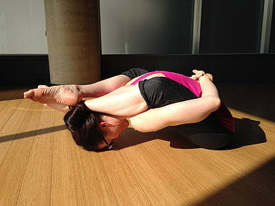woman stretching body on wooden floor