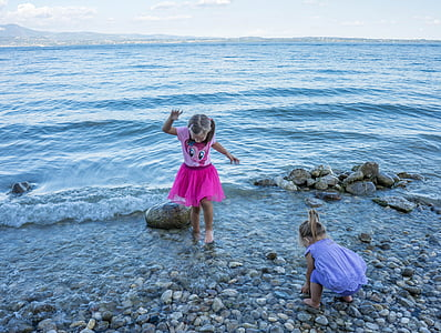 girl in purple and pink dress standing on seashore during daytime