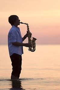 man playing saxophone standing on body of water during golden hour