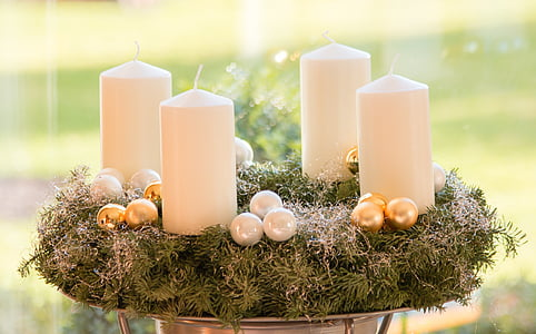 four white pillar candles on top of green wreath