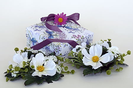 white petaled flowers beside purple box