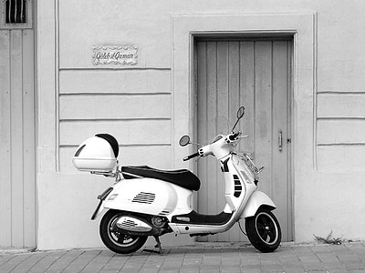 motor scooter parked beside closed door grayscale photography