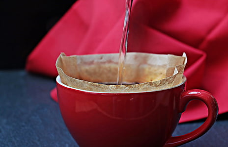 photography of water pouring into a red mug