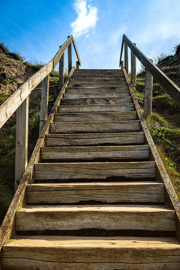 brown wooden stairs under white cloudy sky