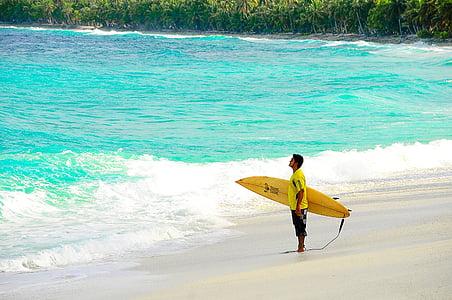 man holding yellow surfboard on beach