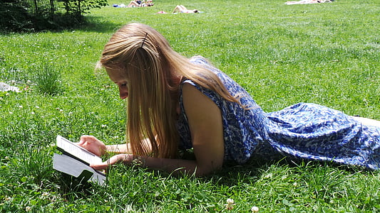 woman in blue floral sleeveless dress lying on grass