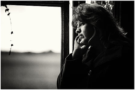 grayscale photo of a woman looking at the window