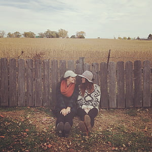 two women leaning on brown wooden fences