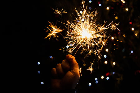 person holding sparkler with background of boke lights