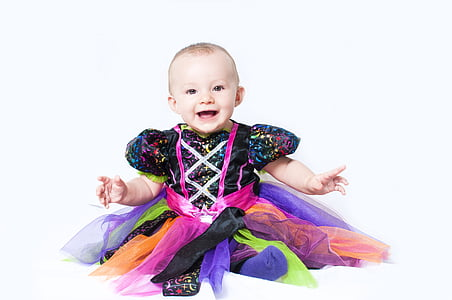 baby wearing multicolored cap-sleeved dress smiling