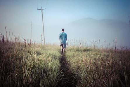 man walks on green grass field