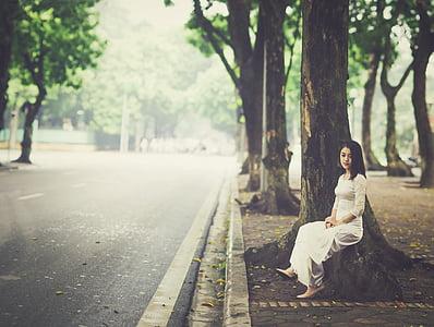 woman in white dress sitting beside tree