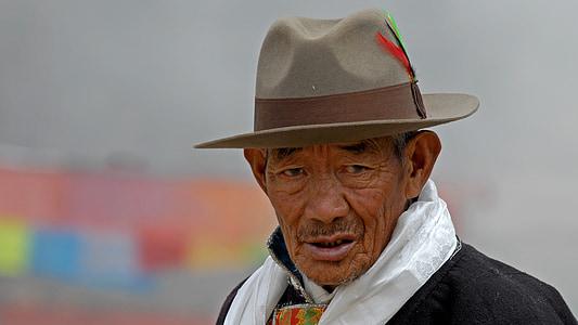 man wearing brown fedora hat and grey scarf