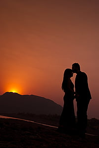 silhouette of man kissing forehead of woman during sunset