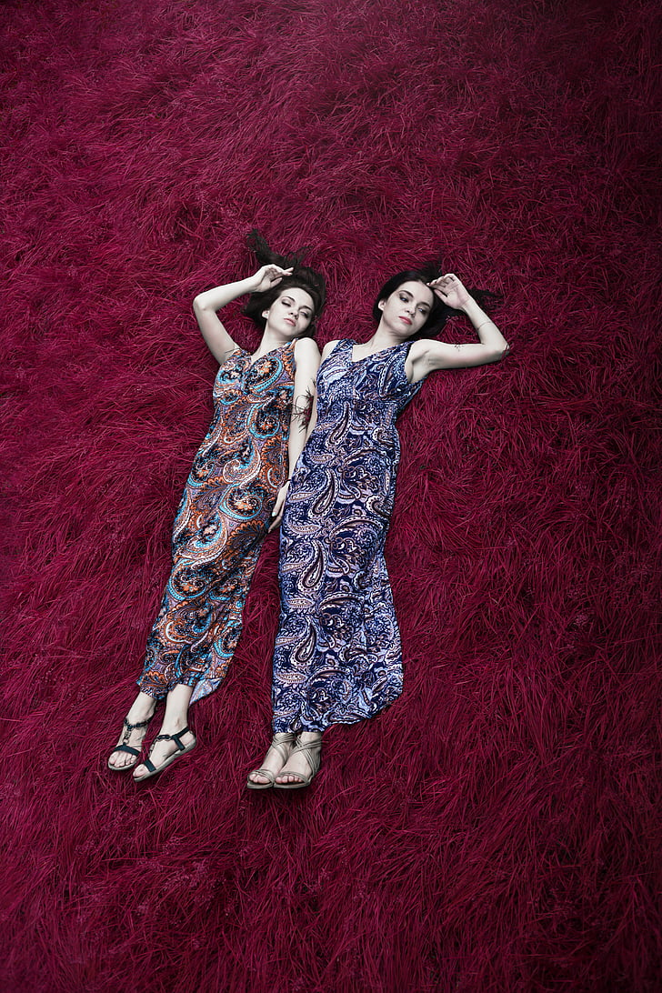 two women wearing multicolored paisley-print dresses lying on red surface