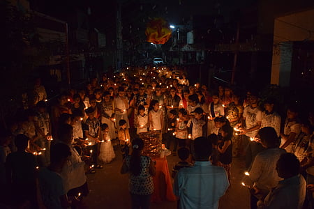 group of people holding candles while huddling