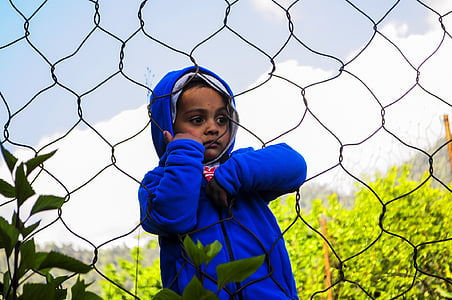 boy wearing blue hoodie holding on link fence