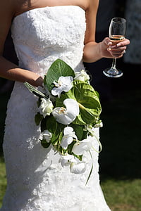 person in white straight across wedding gown holding clear flute glass