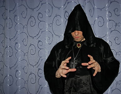 person wearing black robe and silver-colored crucifix necklace using hand gesture