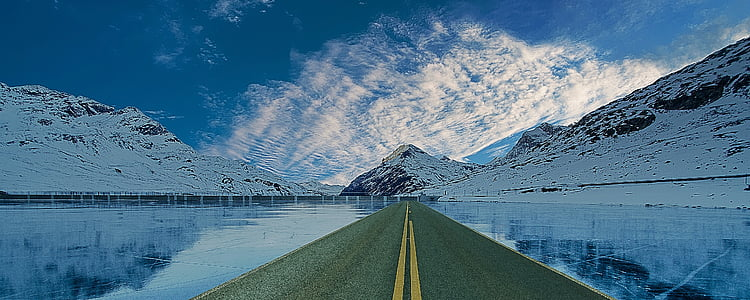 road between body of water during daytime