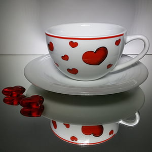 white and red heart-themed ceramic mug on saucer