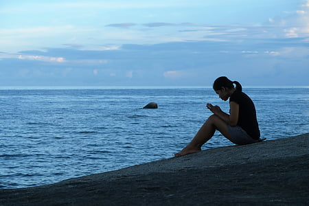 woman sitting beside seashore