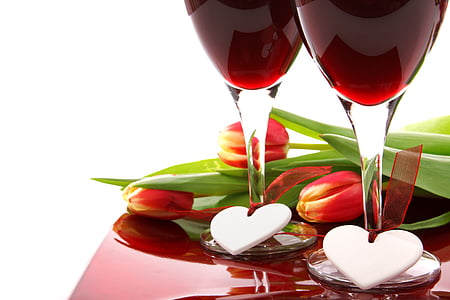 two clear wine glasses near red tulip flowers