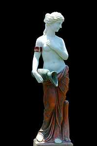 woman in red skirt holding jar with right hand and breast with left hand statue