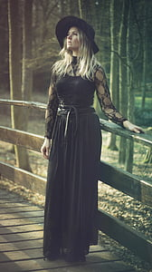woman wearing black lace long-sleeved long dress near brown wooden fence in forest