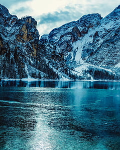 calm body of water near mountain covered by snow under white cloudy sky at daytime