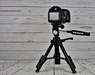 black camera with tripod stand near wall