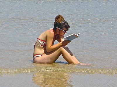 woman wearing white-and-red bikini reading book in seashore