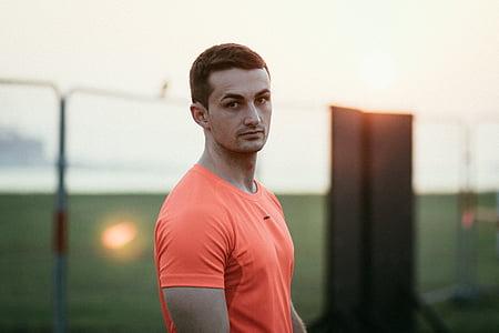man wearing orange crew-neck shirt