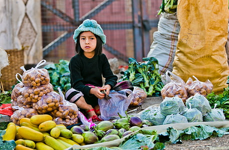 girl sitting in front of vegetables