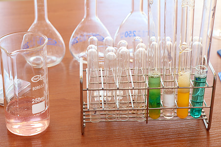 clear glass test tubes set with stainless steel rack near measuring cup