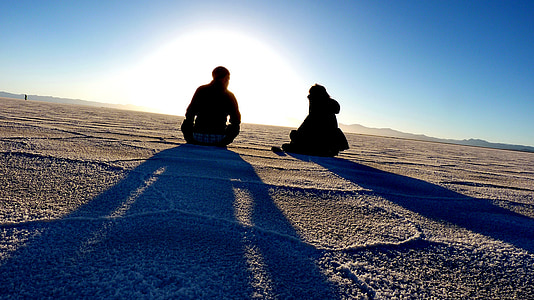 man and woman sitting on desert against the sun