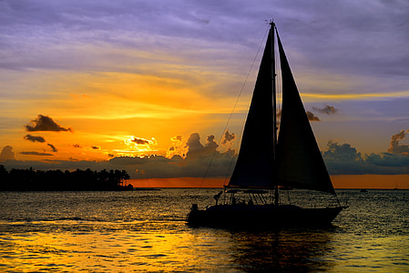 silhouette of sailboat on ocean water during orange sunset