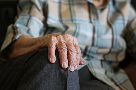 selective focus photo of person with wrinkled hand