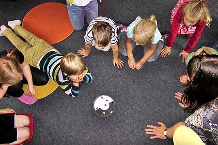 children looking gathering around toy